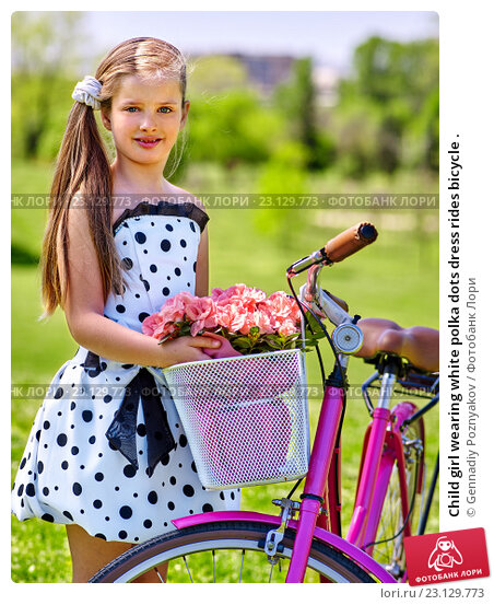 Купить «Child girl wearing white polka dots dress rides bicycle .», фото № 23129773, снято 16 апреля 2016 г. (c) Gennadiy Poznyakov / Фотобанк Лори