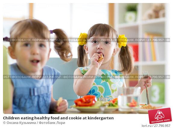 Купить «Children eating healthy food and cookie at kindergarten», фото № 27790957, снято 19 октября 2018 г. (c) Оксана Кузьмина / Фотобанк Лори
