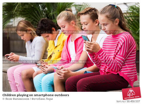 Children playing on smartphone outdoors. Стоковое фото, фотограф Яков Филимонов / Фотобанк Лори