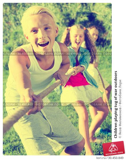Children playing tug of war outdoors. Стоковое фото, фотограф Яков Филимонов / Фотобанк Лори
