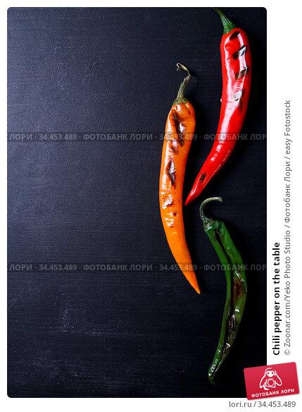 Chili pepper on the table. Стоковое фото, фотограф Zoonar.com/Yeko Photo Studio / easy Fotostock / Фотобанк Лори