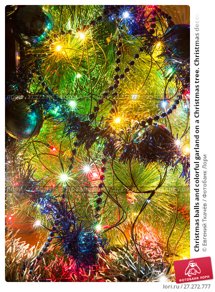 Купить «Christmas balls and colorful garland on a Christmas tree. Christmas decorations», фото № 27272777, снято 19 января 2016 г. (c) Евгений Ткачёв / Фотобанк Лори