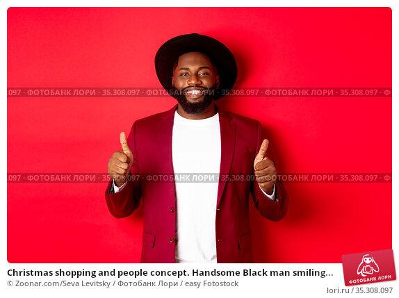 Christmas shopping and people concept. Handsome Black man smiling... Стоковое фото, фотограф Zoonar.com/Seva Levitsky / easy Fotostock / Фотобанк Лори