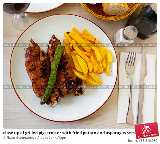 close up of grilled pigs trotter with fried potato and asparagus served on white plate on wooden table. Стоковое фото, фотограф Яков Филимонов / Фотобанк Лори