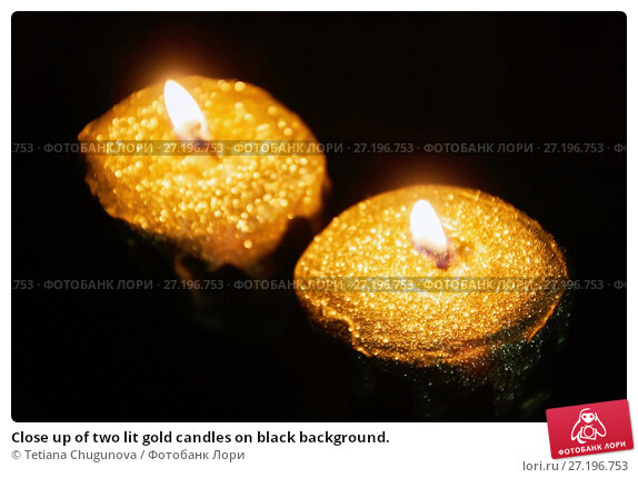 Купить «Close up of two lit gold candles on black background.», фото № 27196753, снято 12 мая 2017 г. (c) Tetiana Chugunova / Фотобанк Лори