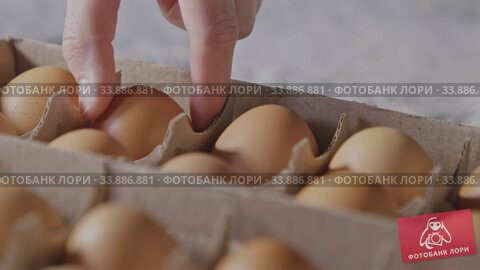 Купить «Close-up view girl's hand takes one egg from paper container. Slow motion, Full HD video, 240fps, 1080p. Process preparing of homemade bake.», видеоролик № 33886881, снято 12 июля 2020 г. (c) Ярослав Данильченко / Фотобанк Лори
