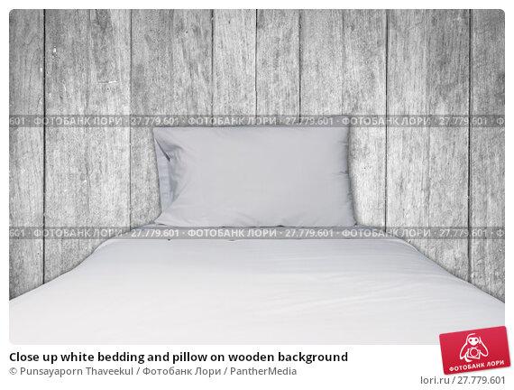 Купить «Close up white bedding and pillow on wooden background», фото № 27779601, снято 26 марта 2019 г. (c) PantherMedia / Фотобанк Лори