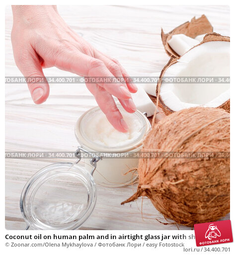 Coconut oil on human palm and in airtight glass jar with shell pieces... Стоковое фото, фотограф Zoonar.com/Olena Mykhaylova / easy Fotostock / Фотобанк Лори