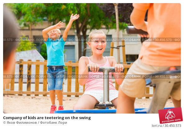 Company of kids are teetering on the swing. Стоковое фото, фотограф Яков Филимонов / Фотобанк Лори