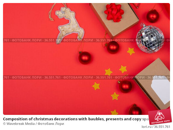 Composition of christmas decorations with baubles, presents and copy space on red background. Стоковое фото, агентство Wavebreak Media / Фотобанк Лори