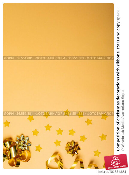 Composition of christmas decorations with ribbons, stars and copy space on yellow background. Стоковое фото, агентство Wavebreak Media / Фотобанк Лори