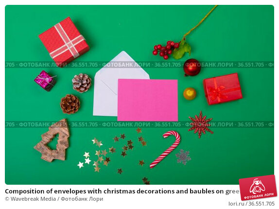 Composition of envelopes with christmas decorations and baubles on green background. Стоковое фото, агентство Wavebreak Media / Фотобанк Лори