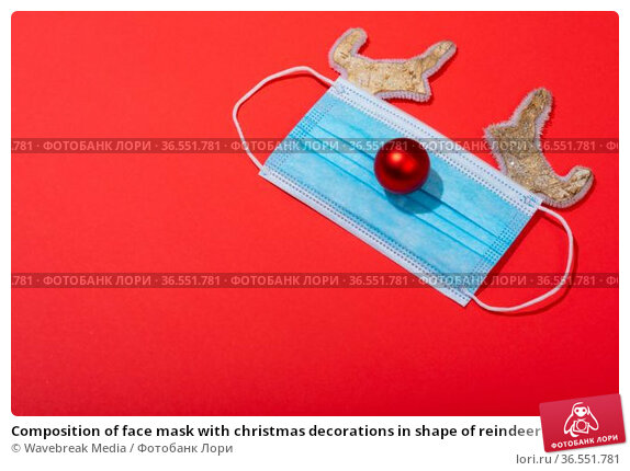 Composition of face mask with christmas decorations in shape of reindeer on green background. Стоковое фото, агентство Wavebreak Media / Фотобанк Лори