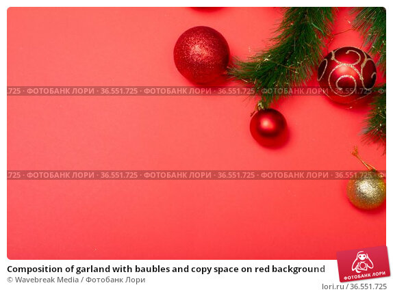 Composition of garland with baubles and copy space on red background. Стоковое фото, агентство Wavebreak Media / Фотобанк Лори