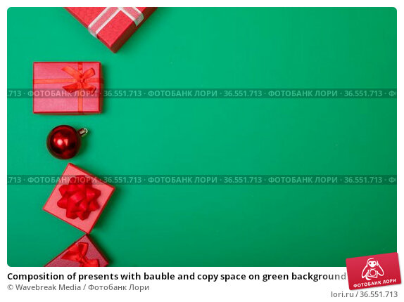Composition of presents with bauble and copy space on green background. Стоковое фото, агентство Wavebreak Media / Фотобанк Лори