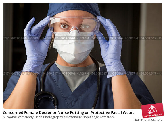 Concerned Female Doctor or Nurse Putting on Protective Facial Wear. Стоковое фото, фотограф Zoonar.com/Andy Dean Photography / age Fotostock / Фотобанк Лори