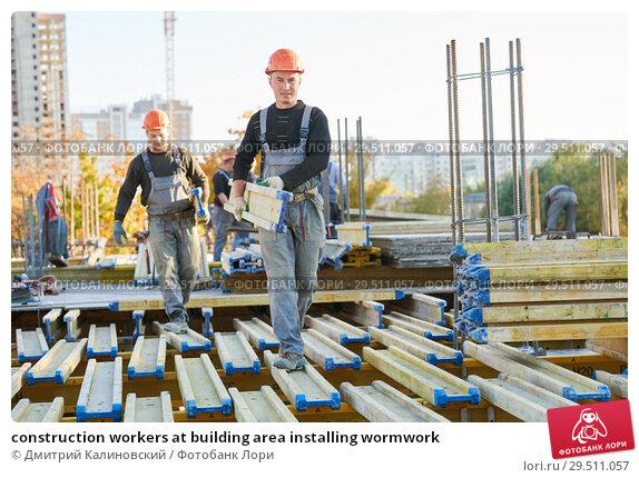 Купить «construction workers at building area installing wormwork», фото № 29511057, снято 12 октября 2018 г. (c) Дмитрий Калиновский / Фотобанк Лори