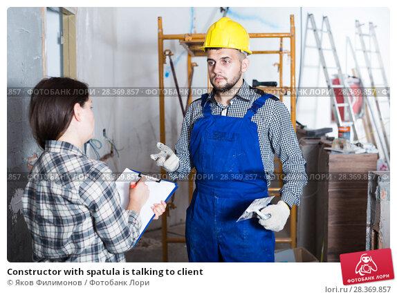 Купить «Constructor with spatula is talking to client», фото № 28369857, снято 3 июня 2017 г. (c) Яков Филимонов / Фотобанк Лори