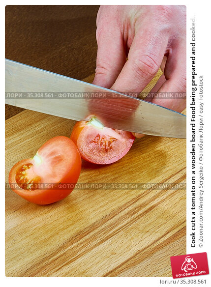 Cook cuts a tomato on a wooden board Food being prepared and cooked... Стоковое фото, фотограф Zoonar.com/Andrey Sergeiko / easy Fotostock / Фотобанк Лори