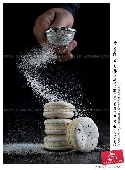 Cook sprinkles macaroon on black background. Close up. Стоковое фото, фотограф Александр Иванов / Фотобанк Лори