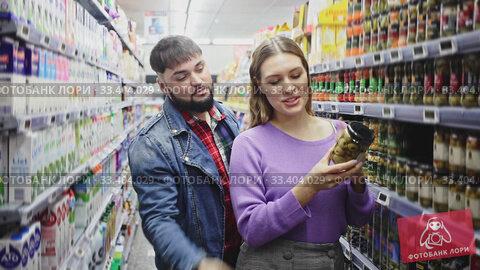 Couple choosing spanish green olives during grocery shopping at food department in supermarket. Стоковое видео, видеограф Яков Филимонов / Фотобанк Лори