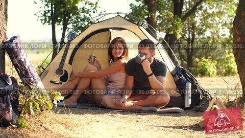 Купить «Couple drinking tea at campsite tent», видеоролик № 29030053, снято 30 августа 2018 г. (c) Илья Шаматура / Фотобанк Лори
