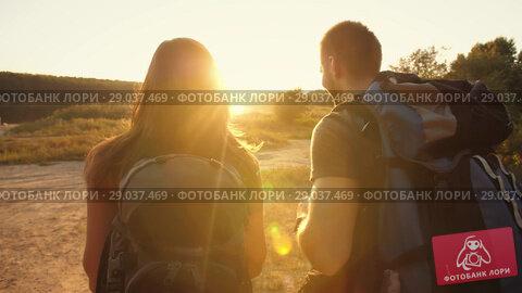 Купить «Couple hiking with backpacks at sunset», видеоролик № 29037469, снято 2 сентября 2018 г. (c) Илья Шаматура / Фотобанк Лори