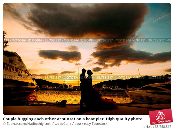 Couple hugging each other at sunset on a boat pier. High quality photo. Стоковое фото, фотограф Zoonar.com/Nadtochiy.com / easy Fotostock / Фотобанк Лори