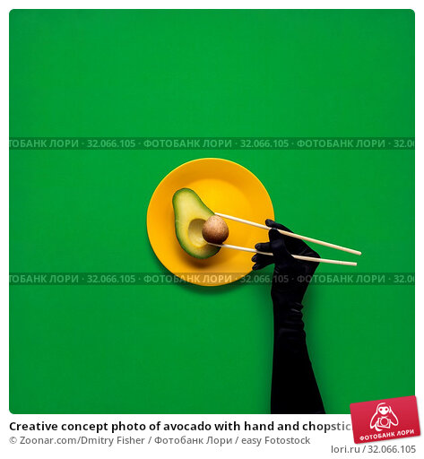 Creative concept photo of avocado with hand and chopsticks on painted plate on green background. Стоковое фото, фотограф Zoonar.com/Dmitry Fisher / easy Fotostock / Фотобанк Лори