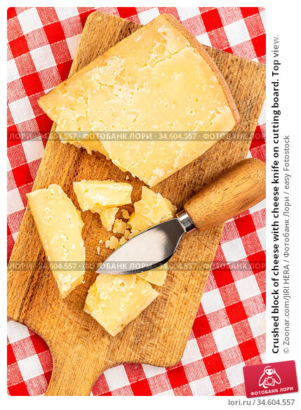 Crushed block of cheese with cheese knife on cutting board. Top view. Стоковое фото, фотограф Zoonar.com/JIRI HERA / easy Fotostock / Фотобанк Лори