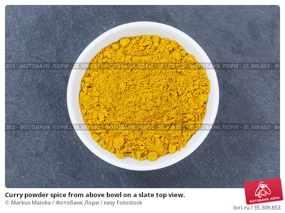 Curry powder spice from above bowl on a slate top view. Стоковое фото, фотограф Markus Mainka / easy Fotostock / Фотобанк Лори