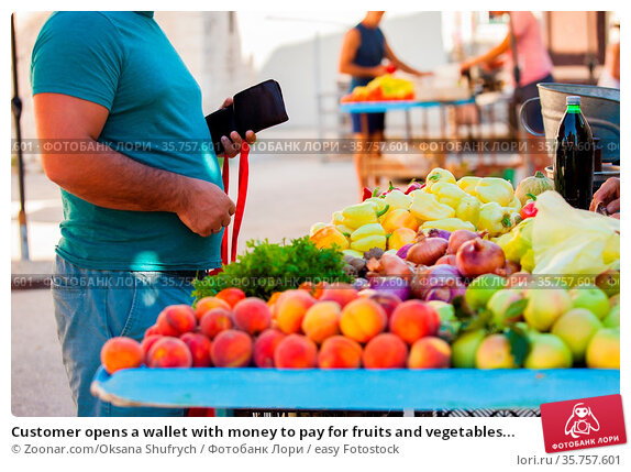 Customer opens a wallet with money to pay for fruits and vegetables... Стоковое фото, фотограф Zoonar.com/Oksana Shufrych / easy Fotostock / Фотобанк Лори