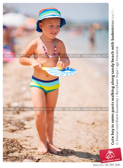 Cute boy in swim pants walking along sandy beach with badminton racket... Стоковое фото, фотограф Zoonar.com/Danil Roudenko / age Fotostock / Фотобанк Лори