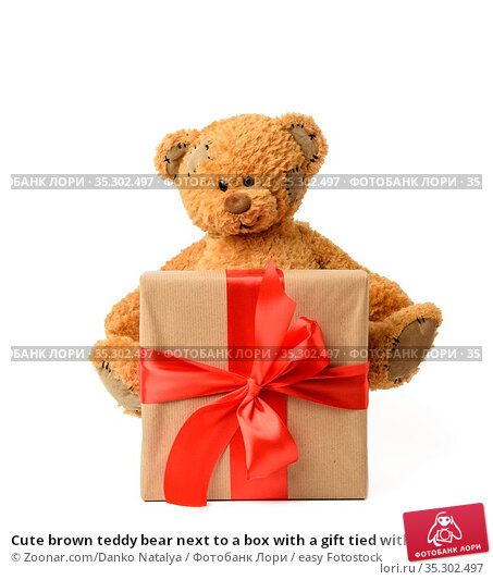 Cute brown teddy bear next to a box with a gift tied with a red silk... Стоковое фото, фотограф Zoonar.com/Danko Natalya / easy Fotostock / Фотобанк Лори
