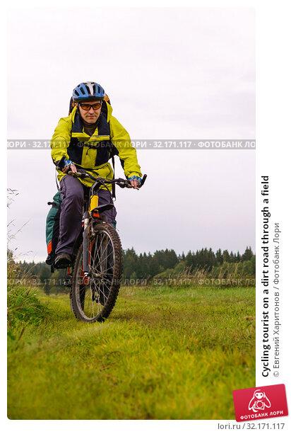 Купить «Cycling tourist on a dirt road through a field», фото № 32171117, снято 3 сентября 2019 г. (c) Евгений Харитонов / Фотобанк Лори