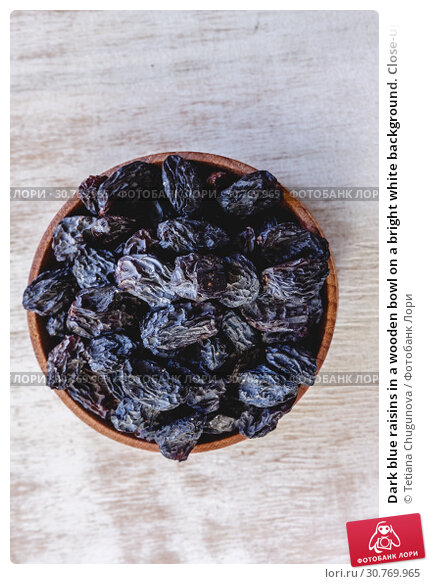 Купить «Dark blue raisins in a wooden bowl on a bright white background. Close-up. Insulated.», фото № 30769965, снято 5 декабря 2018 г. (c) Tetiana Chugunova / Фотобанк Лори