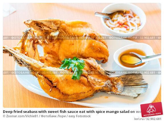 Deep fried seabass with sweet fish sauce eat with spice mango salad on wooden background, Thai groumet cuisine. Стоковое фото, фотограф Zoonar.com/Vichie81 / easy Fotostock / Фотобанк Лори