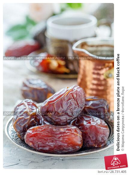 Купить «Delicious dates on a bronze plate and black coffee», фото № 28731405, снято 13 мая 2018 г. (c) Марина Сапрунова / Фотобанк Лори