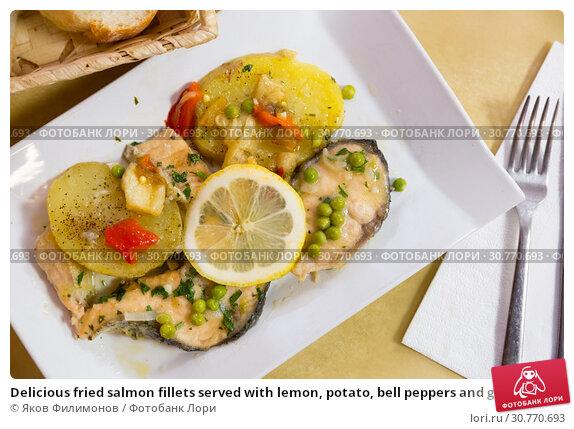 Купить «Delicious fried salmon fillets served with lemon, potato, bell peppers and greens peas», фото № 30770693, снято 26 июня 2019 г. (c) Яков Филимонов / Фотобанк Лори