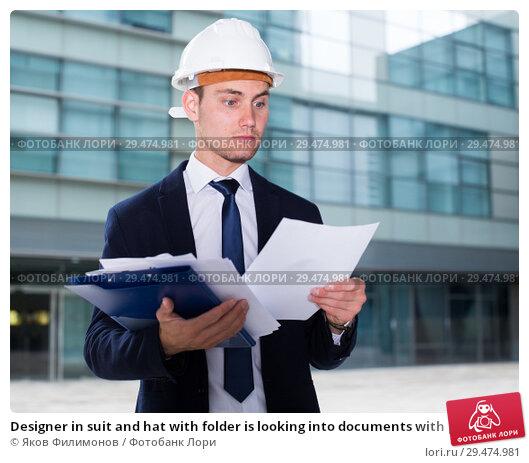 Купить «Designer in suit and hat with folder is looking into documents with project», фото № 29474981, снято 3 июня 2017 г. (c) Яков Филимонов / Фотобанк Лори