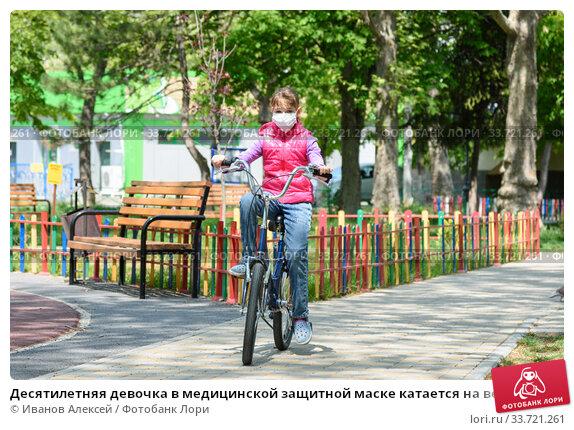 Десятилетняя девочка в медицинской защитной маске катается на велосипеде. Стоковое фото, фотограф Иванов Алексей / Фотобанк Лори