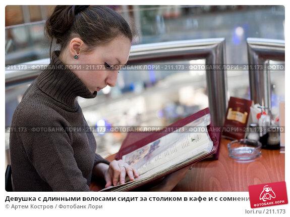 Девушка с длинными волосами сидит за столиком в кафе и с сомнением смотрит в меню, фото № 211173, снято 27 февраля 2008 г. (c) Артем Костров / Фотобанк Лори