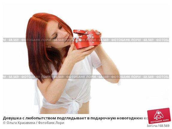Девушка с любопытством подглядывает в подарочную новогоднюю коробку с подарком, фото № 68569, снято 29 июля 2007 г. (c) Ольга Красавина / Фотобанк Лори