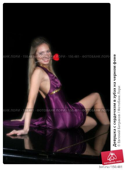 Купить «Девушка с сердечком в зубах на черном фоне», фото № 150481, снято 4 февраля 2007 г. (c) Евгений Батраков / Фотобанк Лори