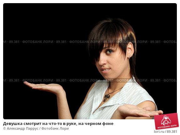 Девушка смотрит на что-то в руке, на черном фоне, фото № 89381, снято 31 мая 2007 г. (c) Александр Паррус / Фотобанк Лори