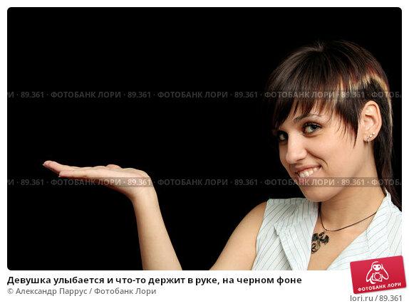 Девушка улыбается и что-то держит в руке, на черном фоне, фото № 89361, снято 31 мая 2007 г. (c) Александр Паррус / Фотобанк Лори