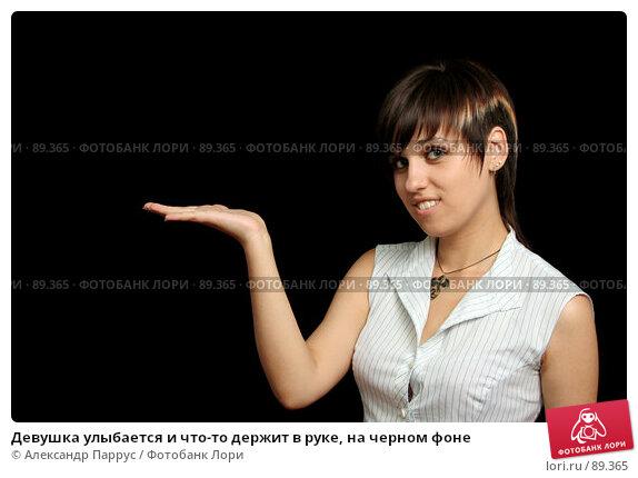 Девушка улыбается и что-то держит в руке, на черном фоне, фото № 89365, снято 31 мая 2007 г. (c) Александр Паррус / Фотобанк Лори