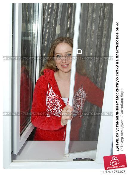 Купить «Девушка устанавливает москитную сетку на пластиковое окно», фото № 763073, снято 21 марта 2009 г. (c) Тимур Ахмадулин / Фотобанк Лори