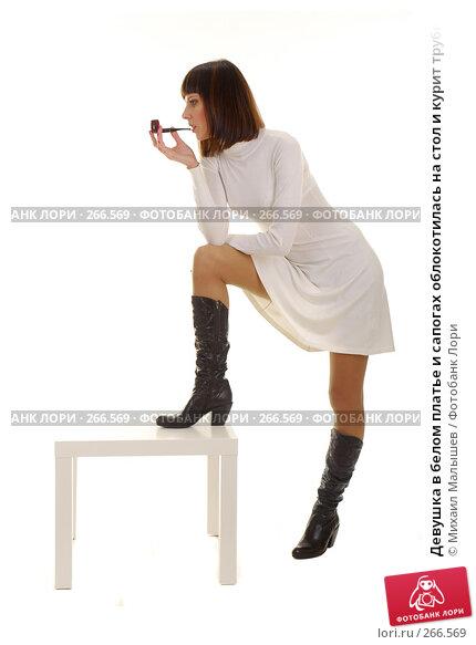 Девушка в белом платье и сапогах облокотилась на стол и курит трубку, фото № 266569, снято 19 января 2008 г. (c) Михаил Малышев / Фотобанк Лори