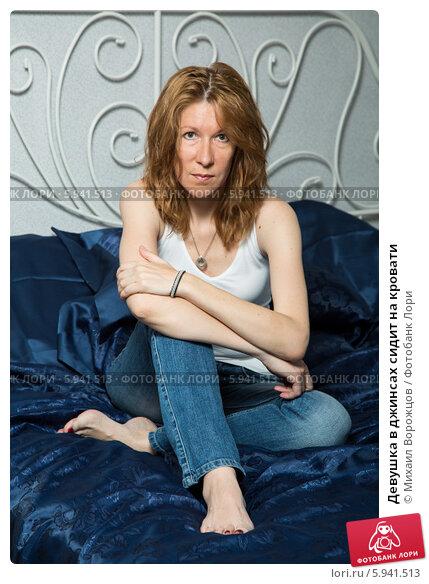 Купить «Девушка в джинсах сидит на кровати», фото № 5941513, снято 12 июня 2013 г. (c) Михаил Ворожцов / Фотобанк Лори